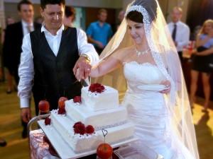 Hochzeitstorte mit Rosen in bordeaux wird vom Brautpaar angeschnitten.